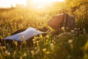 glad tjej ligger bland de vilda blommorna foto