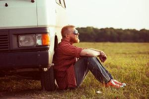 föraren sitter bredvid sin bil foto