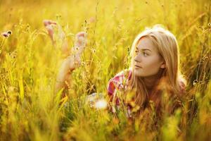 glad tjej i ett fält med gräs och blommor foto