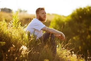 man sitter på gräset på kvällen foto