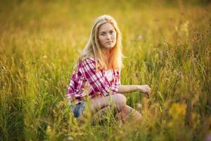 vacker flicka sitter i gräset foto