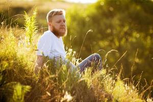 rödskäggig man som sitter på gräset foto