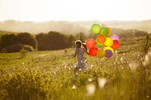 glad liten flicka som springer över fältet foto