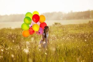 flicka med ett gäng ballonger foto