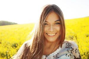 glad tjej i ett fält av gula blommor foto
