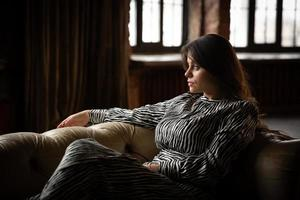 vacker flicka sitter i soffan foto