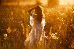 flicka står på ett fält vid solnedgången foto