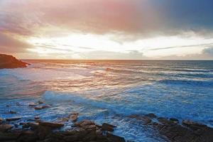 landskap med solnedgång och havsvågor foto