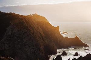 landskap med en fyr som står på ett berg foto