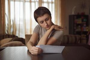 vacker kvinna som läser ett brev vid bordet foto