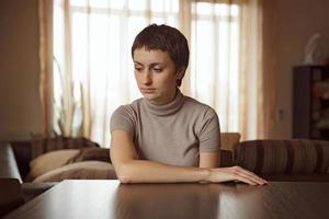 vacker ledsen kvinna som sitter vid bordet foto