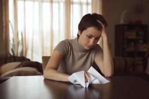 ung ledsen kvinna som håller ett skrynkligt brev foto