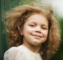 glad vacker glad lockig liten flicka foto