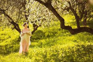 glad ung kvinna som luktar en blomma på ett äppelträd foto