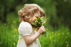 liten flicka som luktar en bukett blommor foto
