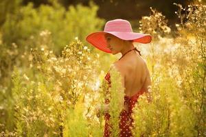 vacker kvinna går bland höga vildblommor foto