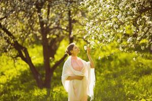 glad ung kvinna som luktar ett blommaäpple foto
