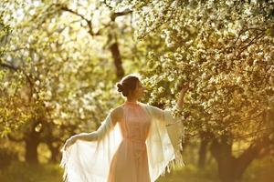 kvinna i en klänning nära blommande äppelträd foto