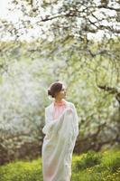 glad kvinna står mitt i en blommande trädgård foto