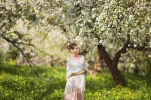 glad ung kvinna bland äppelblom foto