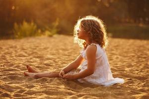 liten flicka i klänning sitter på sanden foto