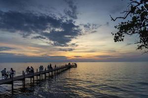 turister ser solnedgången vid piren i Kep Town på Kambodjas kust foto
