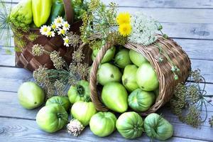 grönsaker i en korg och en bukett vildblommor. foto