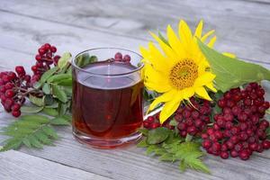 mugg med te bland rönn och solrosor på en träbakgrund. höst foto