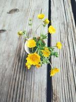gula viola blommor i blå keramik kopp, på trä veranda bakgrund. stilleben i rustik stil. närbild. sommar eller vår i trädgården, landsbygdens livsstilskoncept. vertikal bild foto