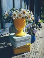 blommig sammansättning av tusensköna blommor och gamla burkar, på blå träverandabakgrund, utomhus och rymden, morgonträdgård, naturligt ljus och skuggor, dagsljus. färgglatt stilleben i rustik stil foto