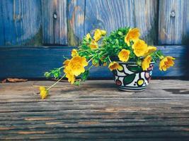 gula färska vilda blommor i färgglada keramiska vas, på blå trä veranda bakgrund. stilleben i rustik stil. närbild. vår eller sommar i trädgården, landsbygdens livsstilskoncept. kopiera utrymme foto