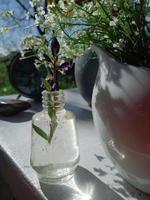 vilda färska blommor i porslinskanna, gammal klocka, på vit trästol, grönt gräs och blå himmelbakgrund. dagsljus, hårda skuggor. stilleben i rustik stil. landsbygdens livsstilskoncept foto