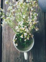 vilda färska blommor i porslinskanna, på blå träbakgrund. dagsljus. stilleben i rustik stil. landsbygdens livsstil, semester, semester koncept. selektivt fokus ovanifrån foto