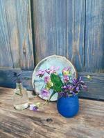 lila vilda blommor i blå keramisk vas, på träverandabakgrund. stilleben i rustik stil. närbild. sommar eller vår i trädgården, landsbygdens livsstilskoncept. kopiera utrymme foto