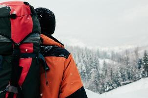 bakifrån av turistman som njuter av bergskoglandskap på en snöig vinterdag. orange plagg, röd ryggsäck. vandring resor extrem livsstil koncept foto