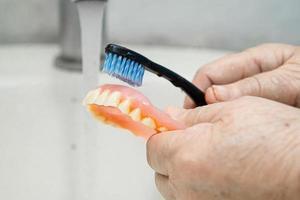 asiatisk senior kvinna patient använder tandborste för att rengöra partiell protes foto