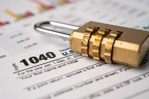 självdeklarationsformulär 1040 och gyllene säkerhets digitala lösenordslåsnyckel foto