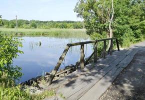 stående gammal träbro över floden i färgad bakgrund foto