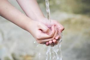 handen fångar vattendroppar som kommer ur kranen foto