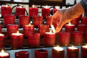 tända ett rött offerljus i en kristen kyrka foto