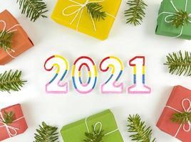 semestervykort med grangrenar, presentförpackningar och 2021 -figurer foto