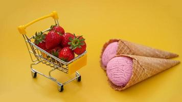 färska jordgubbar i en kundvagn och jordgubbsglass foto