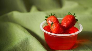 röd jordgubbgelé med bär i en plastbehållare foto