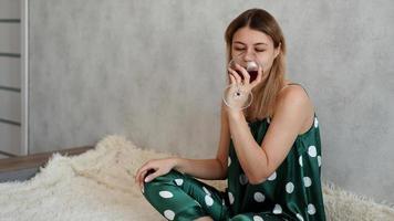 flicka i grön pyjamas i sängen med ett glas rött vin foto