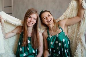 två skrattande unga kvinnor som har roligt när de gömmer sig under den vita filten foto