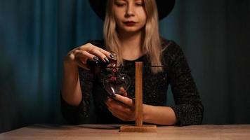 häxan förbereder en dryck. röd kärleksdryck foto