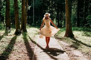en ung kvinna i en vit klänning och en halmhatt går genom skogen foto