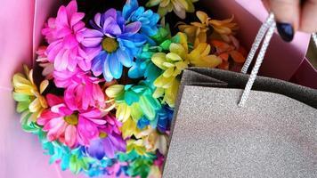 dekorativ komposition - blommor och gåva i silverförpackning foto