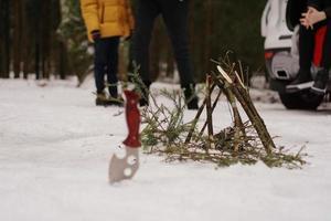 turistkniv och brasa i vinterskogen. foto