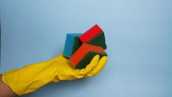 hand i handske som håller några tvättsvampar foto